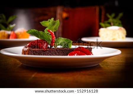 Chocolate cake with strawberry and chili on the side - stock photo