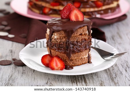 Chocolate cake with strawberry on wooden table close-up - stock photo