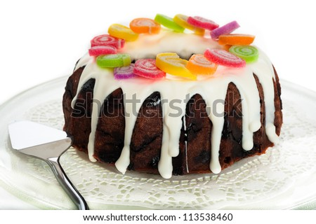 Chocolate cake with white frosting and colorful candies as decoration on white background - stock photo