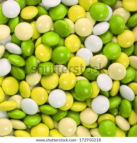 Chocolate candy coated in yellow, green and white. Background