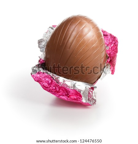 Chocolate candy Easter egg wrapped in pink foil on white background clipping path included - stock photo