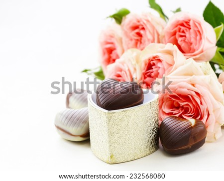 chocolate candy hearts and pink roses for Valentine's day holiday - stock photo