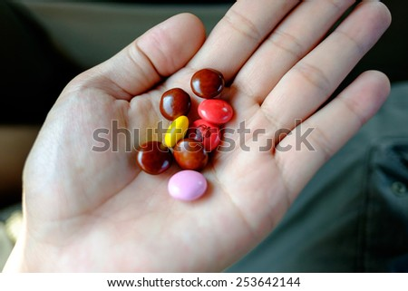 Chocolate candy on the hand. - stock photo
