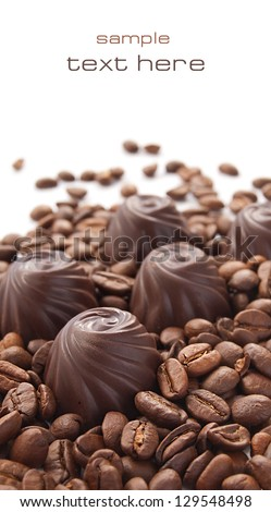 Chocolate candy with coffee beans on a white background - stock photo