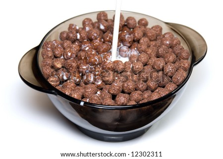 Chocolate cereal with milk in a glass bowl on white background