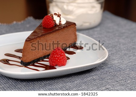 Chocolate cheesecake with raspberries and chocolate sauce on white plate