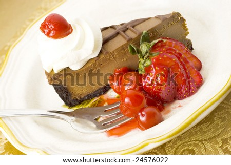 Chocolate Cherry Cheesecake slice on a plate with cherry topping and strawberry garnish, great for Valentine's Day - stock photo