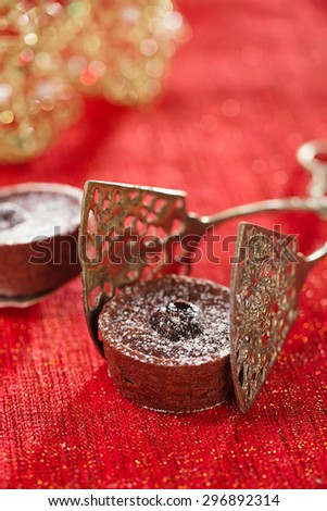 Chocolate Cherry Mini Tartlets in vintage tongs  with festive golden red style, shallow dof - stock photo