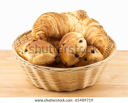 Chocolate chip brioche rolls with croissant in basket - stock photo