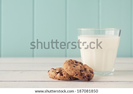 Chocolate chip cookies and a glass of milk on a white wooden table with a robin egg blue background. Vintage look. - stock photo