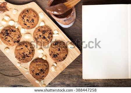 Chocolate chip cookies and macadamia nut with melt chocolate serving wood platter ; copy space for note or recipe  - stock photo