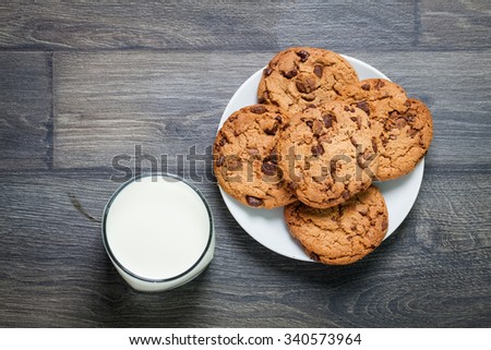 Chocolate chip cookies, milk, rustic wood background, top view  - stock photo