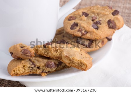 Chocolate chip cookies on a plate with a coffee cup - stock photo