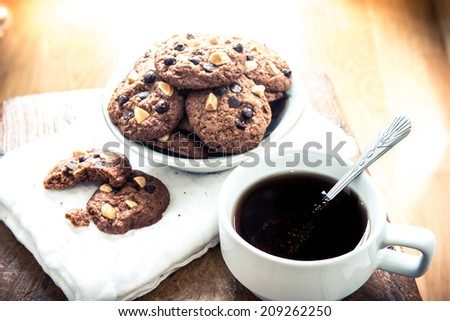 Chocolate chip cookies on napkin and hot tea on wooden table. Stacked chocolate chip cookies close up. split toning color image - stock photo