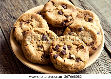 Chocolate chip cookies on plate and rustic wooden table