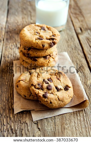 Chocolate chip cookies with milk on paper and rustic wooden table