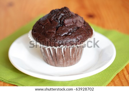 chocolate chip muffin on white plate and green napkin, shallow DOF