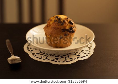 chocolate chip muffin with afternoon light streaming in. - stock photo