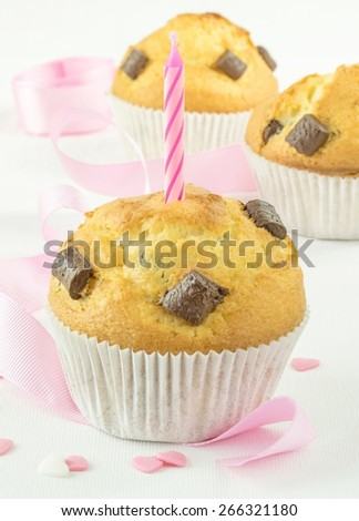 Chocolate chip muffins and birthday candle with pink ribbon and love heart decorations - stock photo