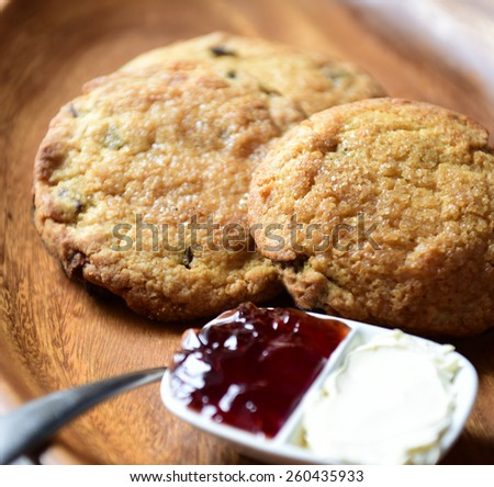Chocolate chip scones on wood serving platter with dish of clotted cream & jam in soft window light