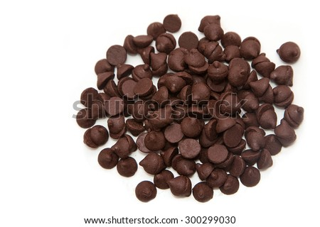 Chocolate chips in wooden spoon on white background - stock photo