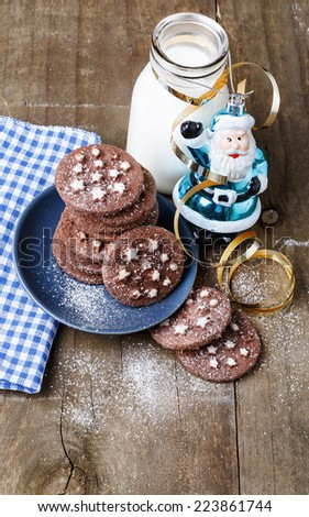 Chocolate Christmas cookies on a blue plate with Christmas ornaments and bottle of milk over rustic wooden background  - stock photo