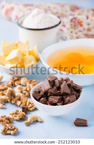 Chocolate chunks, eggs, butter, nuts and cup of flour. Ingredients for baking. Selective focus - stock photo