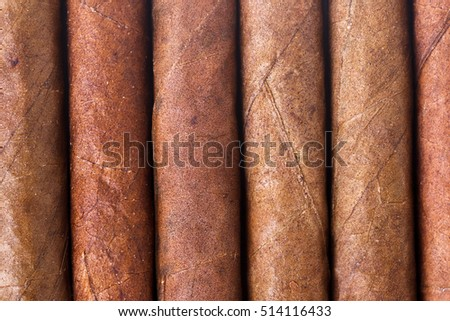 Chocolate cigars in row as background.