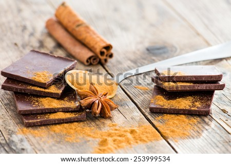 Chocolate, cinnamon and anise beside the wooden table. - stock photo