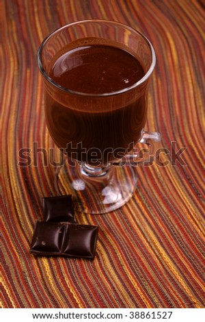 Chocolate cocktail in a glass on a colour background