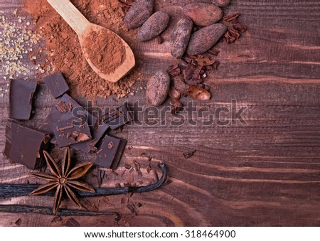 Chocolate, cocoa beans, cocoa powder and spices on the wooden table, top view - stock photo