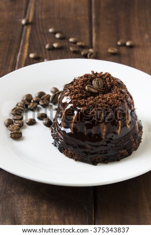 Chocolate Coffee Cake on a white plate with coffee beans on a dark wooden table