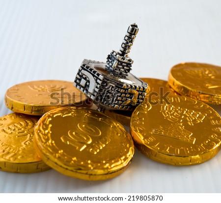 Chocolate coins and silver dreidel for Hanukkah celebration. - stock photo