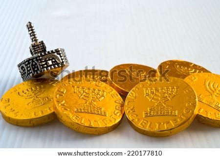 Chocolate coins and silver dreidel for Jewish Hanukkah celebration. - stock photo