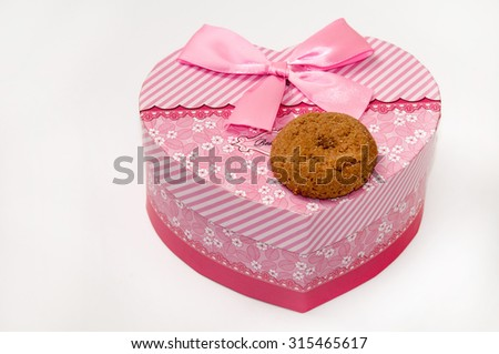 Chocolate cookie and heart shaped pink box with bow.