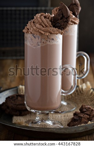 Chocolate cookie milkshake in tall mugs with chocolate whipped cream