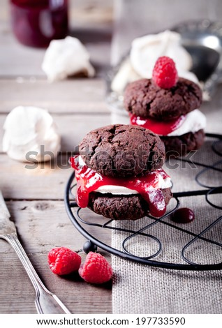 Chocolate cookie sandwich with a raspberry jam and meringue  - stock photo