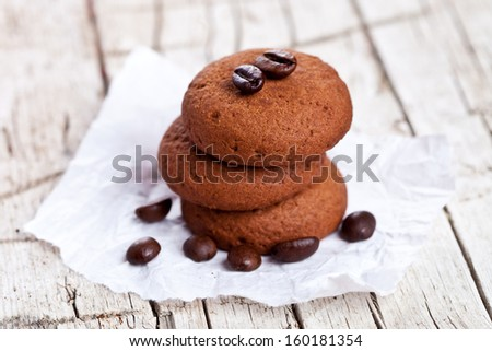 chocolate cookies and coffee beans on rustic wooden background - stock photo