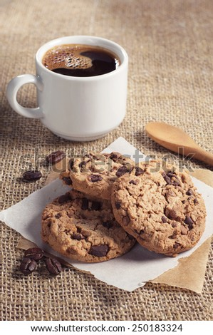 Chocolate cookies and cup of hot coffee on burlap background - stock photo