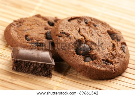 Chocolate cookies and pieces of porous chocolate on mat. - stock photo