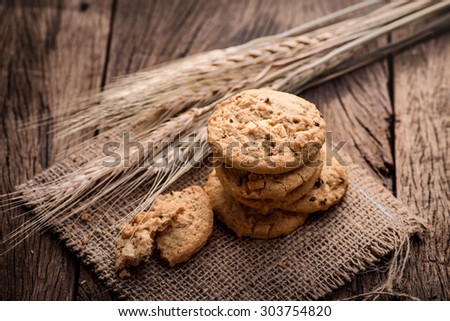 Chocolate cookies on white linen napkin on wooden table. Chocolate chip cookies shot on sack - stock photo