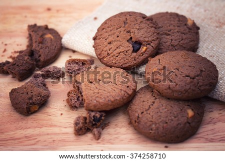 Chocolate cookies on white linen napkin on wooden table. Chocolate cookies. Chocolate chip cookies shot on coffee colored cloth, closeup. selective focus. - stock photo