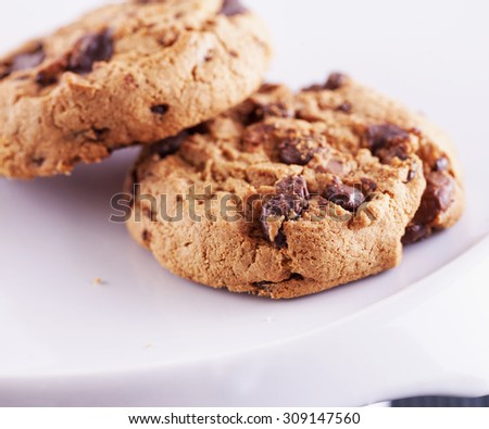Chocolate cookies over white stand, shallow depth of field, horizontal image