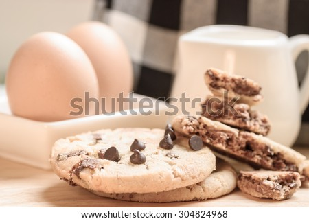 chocolate cookies stack on wooden plate with small jar and fresh egg - stock photo
