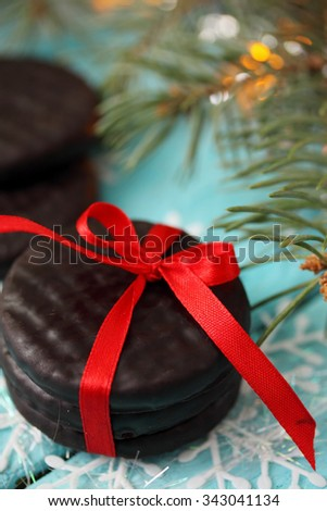Chocolate cookies tied a red ribbon. Gift on a wooden background. Christmas background with copy space.