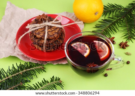 Chocolate cookies with icing on a red saucer orange mulled wine with lemon and spices, twigs of coniferous wood and spices. Christmas celebrating concept - stock photo