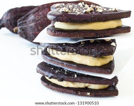 Chocolate cookies with peanut butter filling on white background. - stock photo