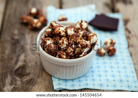 Chocolate covered popcorn in a white bowl on wooden table, dark chocolate at background - stock photo