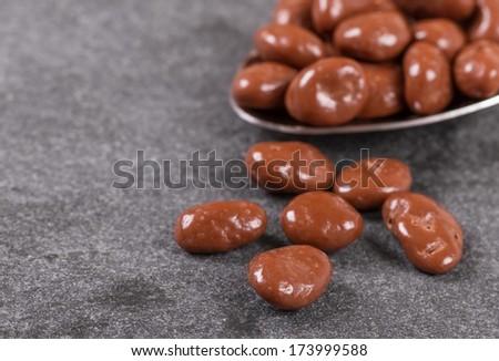Chocolate Covered Raisins on Black Slate Board - stock photo