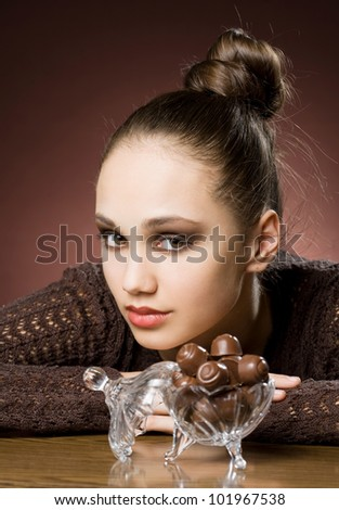 Chocolate cravings, beautiful young brunette with chocolate bonbons. - stock photo